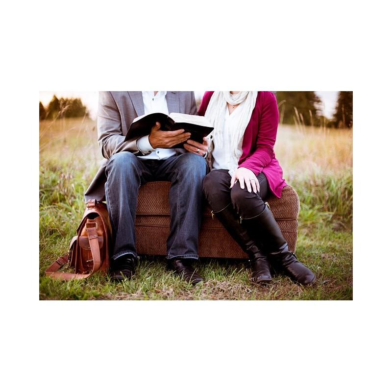 Deux personnes sont assises sur une malette et lisent un livre