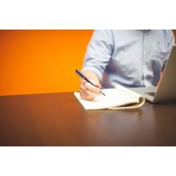 homme écrivant devant un portable