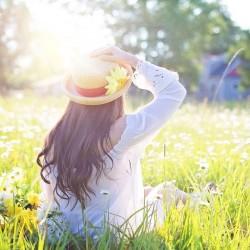 Femme avec chapeau dans un champ