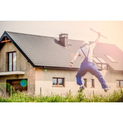 Un homme en tenue de chantier, heureux devant sa maison neuve