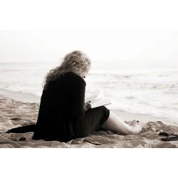 Femme lisant un livre sur une plage
